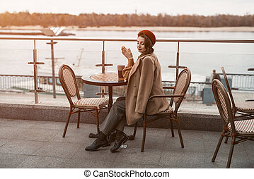 Overall plan of a thoughtful young Parisian woman with a coffee mug on the table wearing red beret sitting on terrace of restaurant or cafe. Autumn urban city on background. Tinted image.