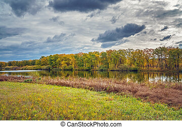 Overcast clouds over a small forest lake in front of beautiful autumn forest
