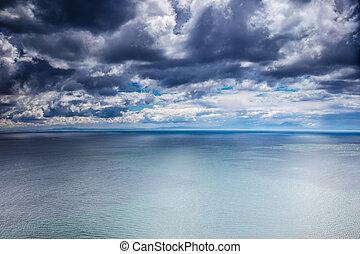 Overcast weather over sea, dark dramatic cloudy sky, dangerous seascape, panoramic landscape