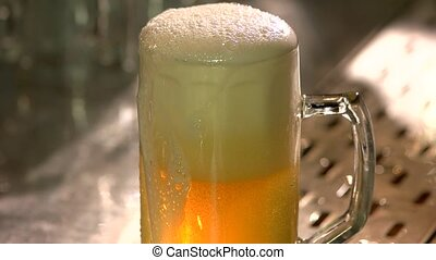 Overfilled dripping glass of beer on the bar table.