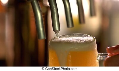 Overflowing glass of beer under tap. Tap beer dripping, slow-mo.
