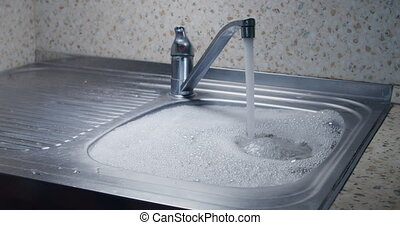 Overflowing kitchen sink with water and foam due to blockage sin