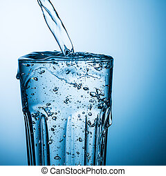 overflowing water glass - A glass of pouring water is...