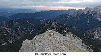 Overflying mountain peak towards sunrise.