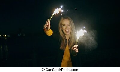 Woman dance with roman candles in her hands in the night street
