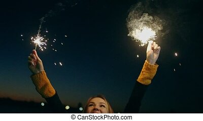 Overhappy woman dancing while holding sparkler. Beautiful...