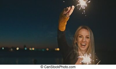 Overhappy woman dancing with burning bengal lights in the...