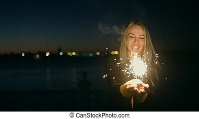 Overhappy woman dancing with some bengal light sparklers in hands in night in front of city skyline with blurred lights