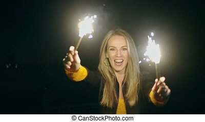 Overhappy woman dancing with two roman candles in her hands in the night street