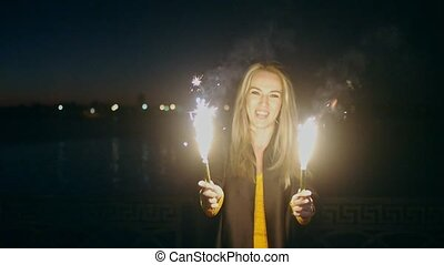 Overhappy woman smiling and holding two roman candle sparklers in her hands