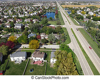 Overhead aerial view of colorful autumn trees residential houses and yards along suburban street in Chicago area. Midwest USA