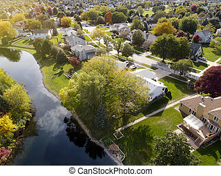 Overhead aerial view of colorful autumn trees residential houses and yards along suburban street