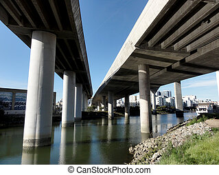 Overhead Highways on columns in the air as they go into the city of San Francisco as they hang over Mission Creek on a nice day in California.