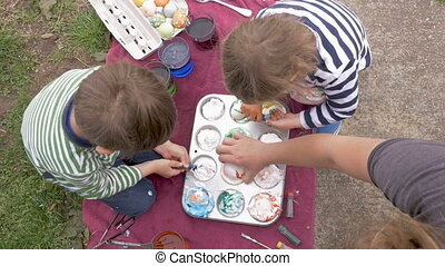Overhead of a young boy and girl working on arts and crafts with mom