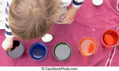 Overhead of a young girl dying easter eggs in colored dye on a towel