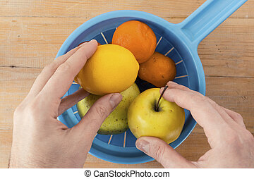 Overhead of Assorted Fruits in a Blue Plastic Strainer