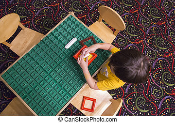 Overhead of Boy Playing With His Toys at Table - Overhead of...