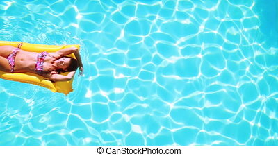 Overhead of brunette lying on lilo in pool on sunny day on...