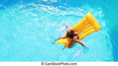 Overhead of brunette sitting on lilo in pool on sunny day on...