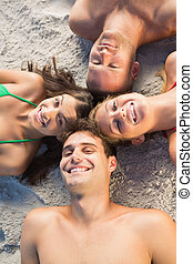 Overhead of cheerful friends lying together in a circle