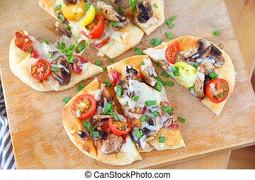 Overhead of naan pizza on cutting board