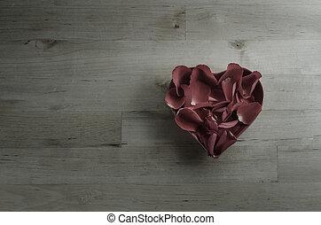 Overhead of Rose Petals Filling Heart Shaped Bowl - Rose...