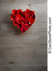 Overhead of Rose Petals in Heart Shaped Bowl on Wood -...