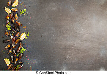 Overhead of row of frilled mussels with lemon and parsley. Healthy food concept. Copy space.