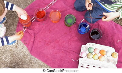 Overhead of young boy and girl coloring easter eggs and...