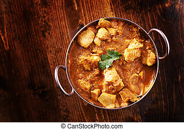 overhead photo of a batli dish with indian butter chicken...