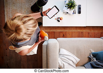 Overhead Shot Looking Down On Woman At Home Checking Phone Message Before Leaving For Fitness Class