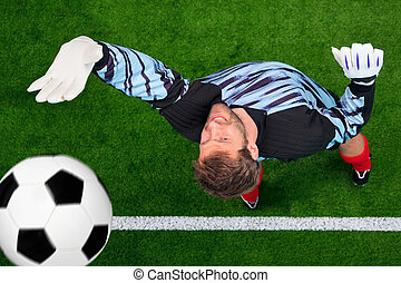 Overhead shot of a goalkeeper missing the ball.