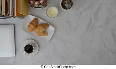 Overhead shot of office room with coffee cup, croissant and office supplies on white table