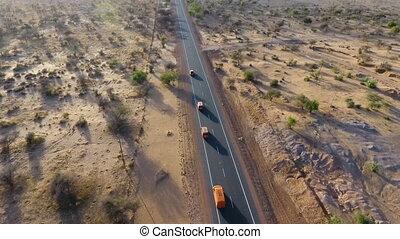 Overhead shot of orange vans driving in the desert