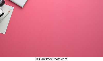 Overhead shot of photographer workspace with camera, stationery and copy space on pink table