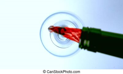 Overhead shot of red wine being poured into glass in slow...
