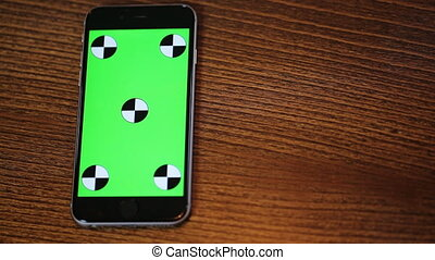 Overhead shot of  smart phone with a green screen on a wooden table with copy space Top view