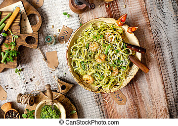 overhead shot of tasty homemade italian pasta with grilled shrimps, pesto sauce, parmesan cheese, fresh basil