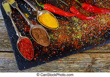 Overhead view depicting cooking with spices in a rustic kitchen with bowls of colourful ground spice and scattered powder on an old wooden