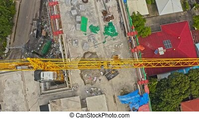 Overhead view of a construction crane loading materials on building site