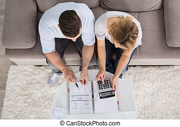 Overhead View Of A Couple Calculating Bills
