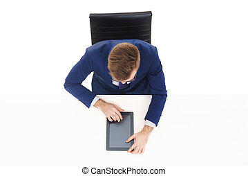Overhead view of a handsome businessman working with tablet computer in office. Business and office concept