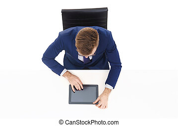 Overhead view of a handsome businessman working with tablet computer in office. Business and office concept.