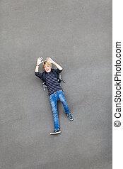 teen boy lying on ground