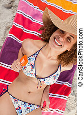 Overhead view of an attractive woman in bikini holding a...