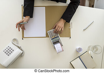Overhead view of businessperson using a calculator