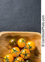 Overhead view of cherry tomatoes in wooden plate