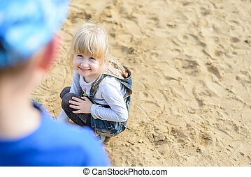 Overhead view of child kneeling in the sand