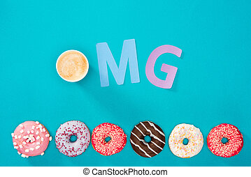 Overhead view of coffee cup, OMG sign and sweet donuts isolated on blue. Appetizing baked donuts background