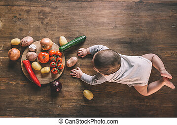 Overhead view of cute baby boy lying on kitchen table near group of vegetables on chopping board